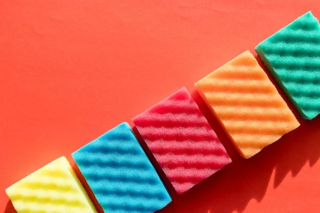 Gekleurde sponzen op rode muur met kopie ruimte. opruimdag. sponsen schoonmaakset. schoonmaakproduct voor het huis. huishoudelijk werk, huishoudelijk en huishoudelijk concept, schoonmaakspullen