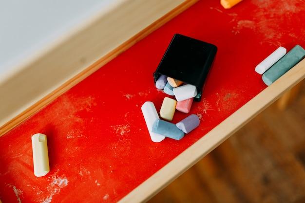 Gekleurde stukjes krijt liggen op een rode standaard voor tekentafels, creatieve puinhoop