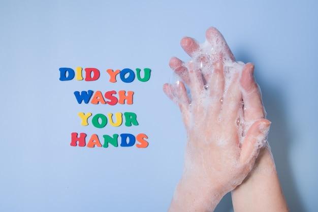 Gekleurde tekst heb je je handen naast je handen gewassen in foam op een gekleurde achtergrond