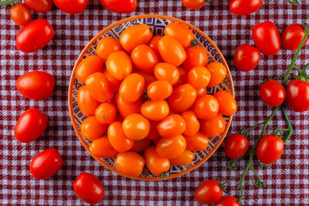 Gekleurde tomaten in een plaat plat lag op een picknick doek ruimte