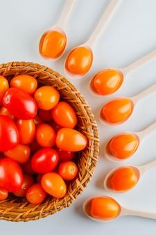 Gekleurde tomaten in houten lepels en mand bovenaanzicht