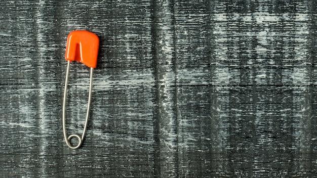 Gekleurde veiligheidsspelden. rode pin op zwarte houten achtergrond met kopie ruimte.
