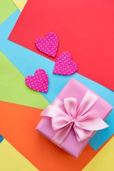 Gekleurde vellen papier decoratief hart valentijnsdag geschenkdoos lint satijnen strik roze.