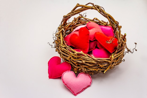 Gekleurde vilt harten in rieten mand geïsoleerd op een witte achtergrond. valentijnsdag of bruiloft romantische concept