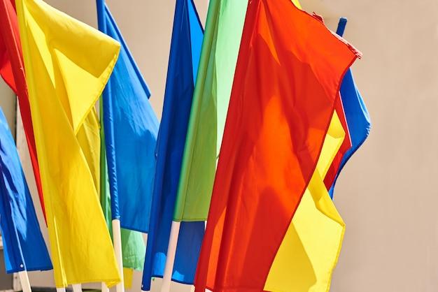 Gekleurde vlaggen op vlaggenmasten die in de wind vliegen