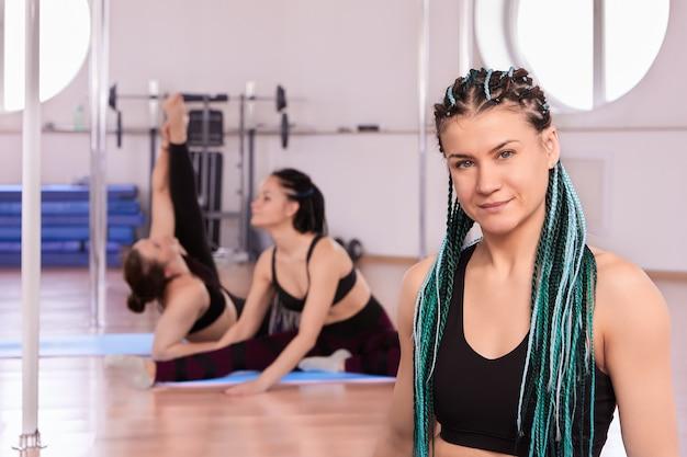 Gekleurde vlechten in kapsel van fitnesstrainer voor vrouwen