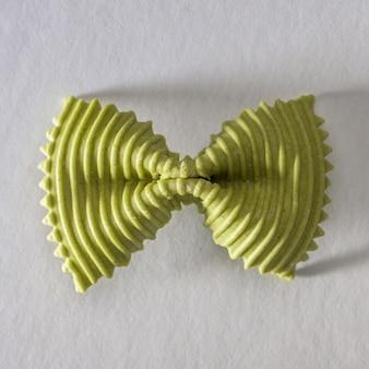 Gekleurde vlinderdas pasta. closeup enkele groene farfalle op grijze achtergrond.