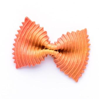 Gekleurde vlinderdas pasta. closeup enkele oranje farfalle geïsoleerd op een witte achtergrond.