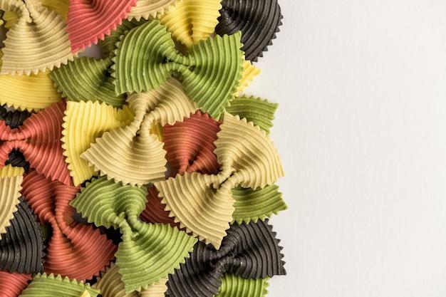 Gekleurde vlinderdas pasta. closeup meerdere farfalle geïsoleerd op een witte achtergrond.