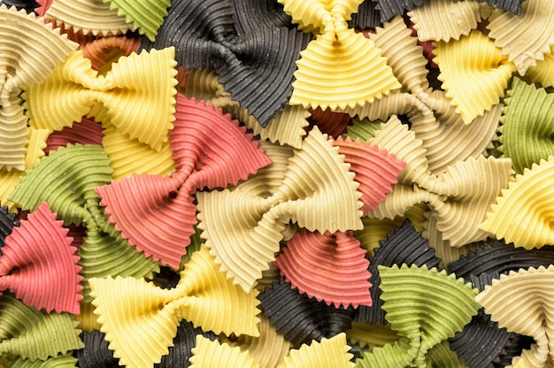 Gekleurde vlinderdas pasta. closeup meerdere farfalle op witte achtergrond.