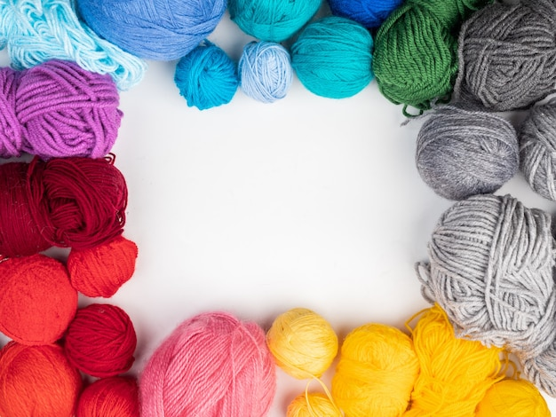 Gekleurde wol voor breien op een witte achtergrond. bovenaanzicht, kopieer ruimte.