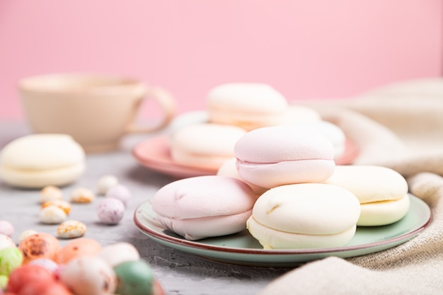 Gekleurde zefier of marshmallow met een kopje koffie en dragees op een grijze en roze achtergrond.