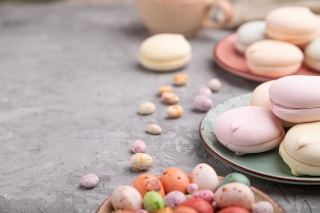 Gekleurde zefier of marshmallow met kopje koffie en dragees op een grijze betonnen achtergrond.