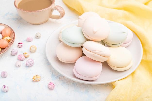Gekleurde zefier of marshmallow met kopje koffie en dragees op witte betonnen achtergrond. zijaanzicht, close-up.