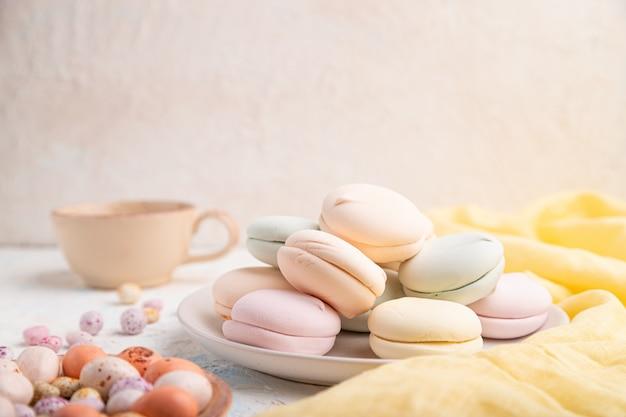 Gekleurde zefier of marshmallow met kopje koffie en dragees op witte betonnen achtergrond. zijaanzicht, kopieer ruimte, selectieve aandacht.