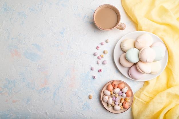 Gekleurde zefier of marshmallow met kopje koffie en dragees op witte betonnen achtergrond.
