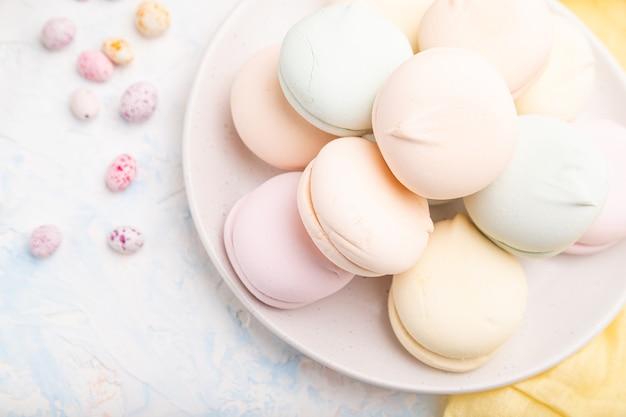 Gekleurde zephyr of marshmallow en dragees op wit betonnen oppervlak en geel textiel