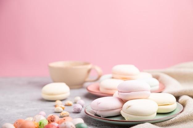 Gekleurde zephyr of marshmallow met kopje koffie en dragees op een grijze en roze achtergrond en linnen textiel.