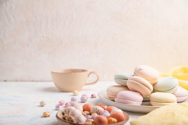 Gekleurde zephyr of marshmallow met kopje koffie en dragees op wit beton