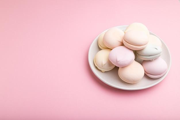 Gekleurde zephyr of marshmallow op pastel roze tafel. zijaanzicht, close-up, kopieer ruimte.