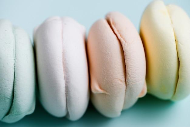 Gekleurde zoete dessert zefier marshmallows op hemel blauwe achtergrond. air marshmallows. close-up, fooffotografie