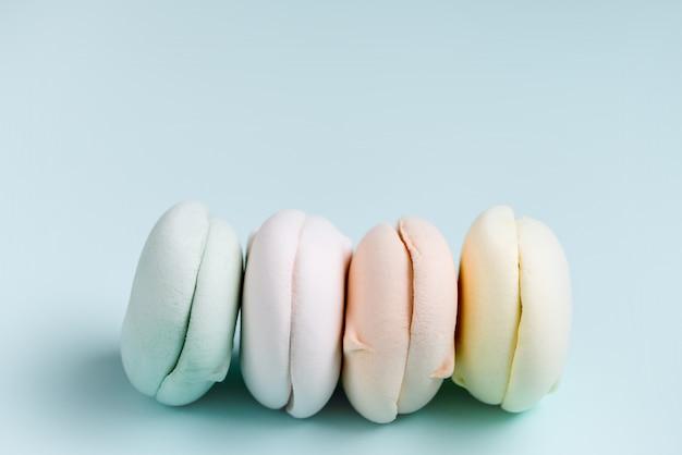 Gekleurde zoete dessert zephyr marshmallows. lucht colrful zefier op blauwe achtergrond, pastelkleuren. close-up, voedselfotografie