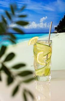 Gekoelde cocktail met citroen en ijs op de achtergrond van het strand, de blauwe zee en de blauwe lucht