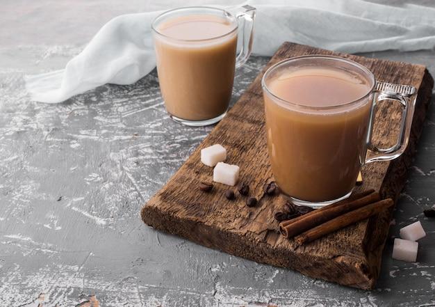 Gekoelde koffie met melk, kaneelstokjes, koffiebonen, suiker, lepel op tafel.