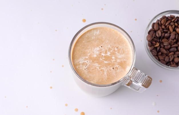 Gekoelde koffie met room naast koffiebonen op een witte achtergrond