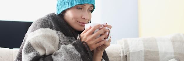 Gekoelde vrouw op bank in deken en hoed houdt warme kop vast