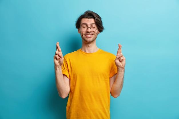 Gekoesterd wensconcept. positieve man met trendy kapsel kruist vingers poses met gesloten ogen bidt voor wonder en hoopt dat er goede dingen gebeuren