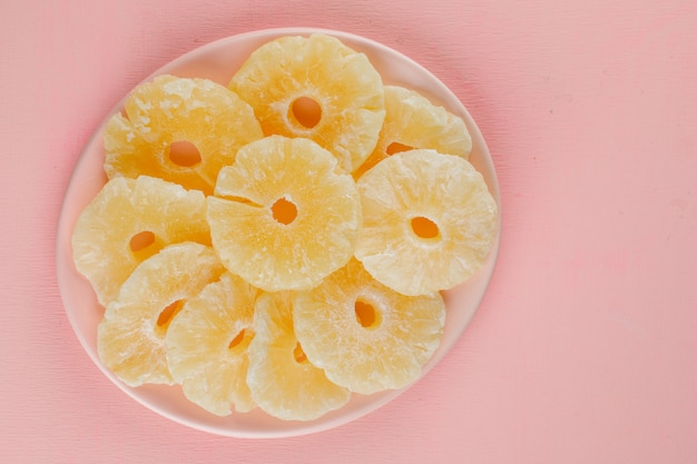 Gekonfijte ananas ringen in een plaat op een roze oppervlak