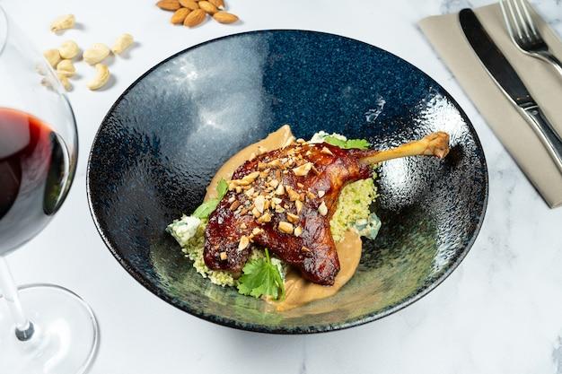 Gekonfijte eendenbout met pindakaas en dor blauwe kaas in stijlvolle donkere kom op marmeren tafel. gourmet lunchgerecht. franse keuken.