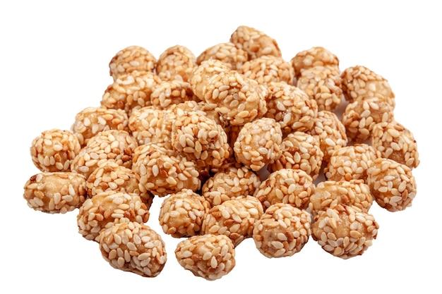 Gekonfijte pinda's in honing en suikerglazuur met sesam op wit