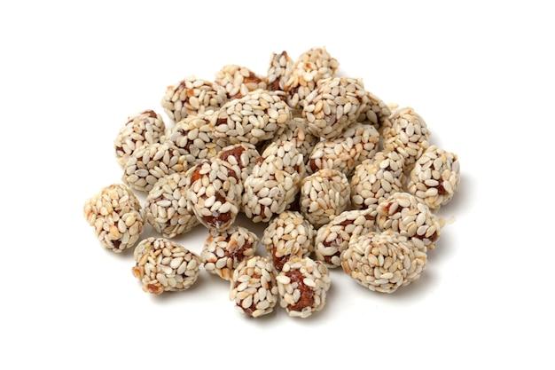 Gekonfijte pinda's in honing en suikerglazuur met sesam op witte achtergrond.