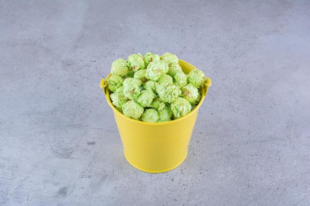 Gekonfijte popcorn opgestapeld in een gele emmer op een marmeren oppervlak