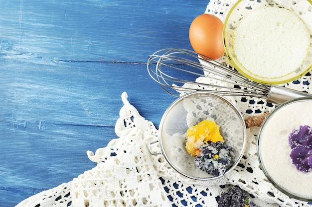 Gekonfijte violette bloemen maken met eiwitten en suiker, op een gekleurd houten oppervlak