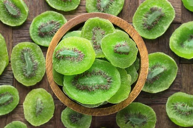Gekonfijte vrucht, gedroogde kiwi met suiker in houten kom, bovenaanzicht.
