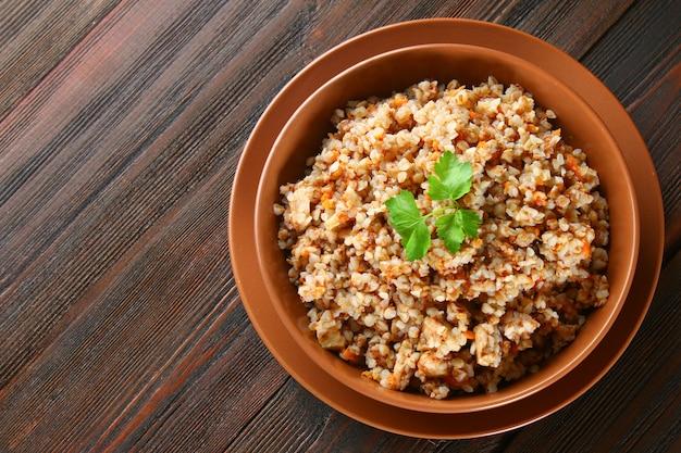 Gekookt boekweit in een kom met stukjes kippenvlees en koriander op een bruine houten tafel.