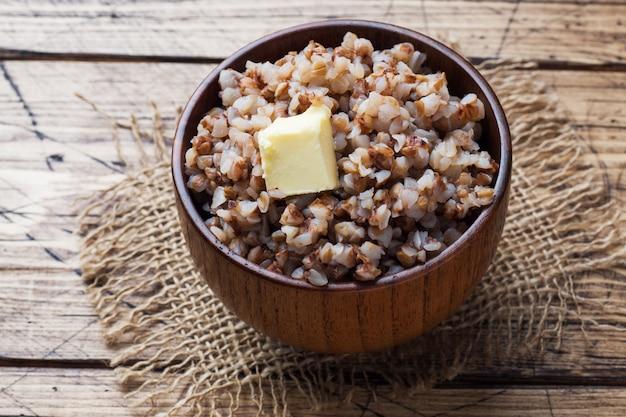 Gekookt boekweit met een stuk boter in een houten kom op een rustieke tafel