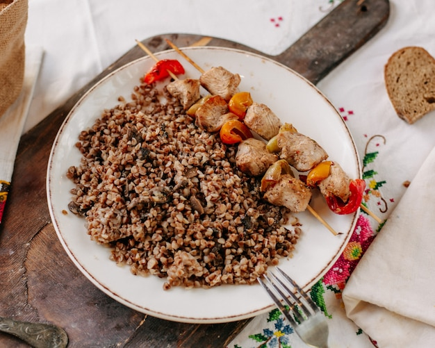 Gekookt boekweit samen met gebakken vlees plakjes op kleine stokjes in witte plaat brood loafs op kleurrijke tissued tafel overdag
