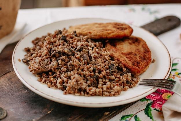 Gekookt boekweit samen met gebakken vlees segmenten in witte plaat brood brood op kleurrijke tissued tafel overdag