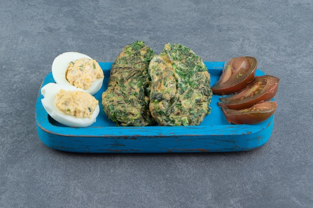 Gekookt ei en gebakken ei met groenen op blauw bord.