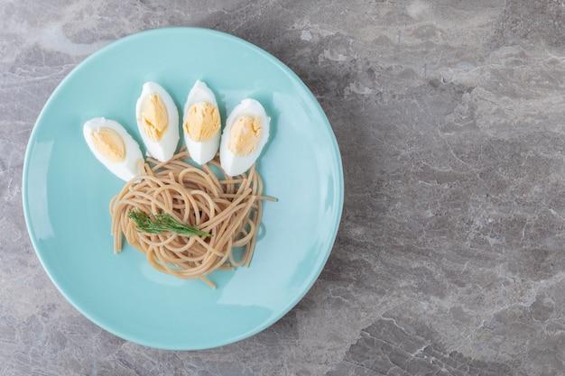 Gekookt ei en spaghetti op blauw bord.