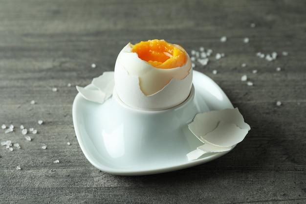 Gekookt ei en zout op grijze gestructureerde achtergrond
