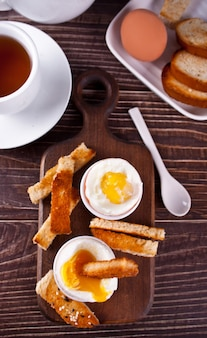 Gekookt ei in eierdopje op houten bord met krokante toast