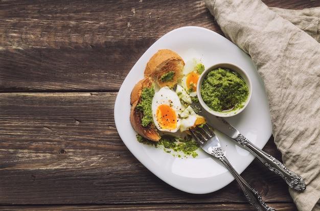 Gekookt ei met geroosterd brood en pestosaus op rustieke houten achtergrond. bovenaanzicht.
