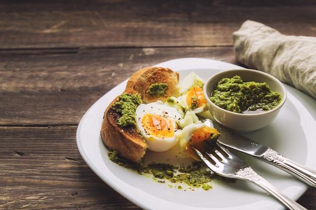 Gekookt ei met geroosterd brood en pestosaus op rustieke houten achtergrond. selectieve aandacht.