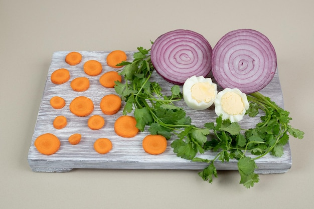 Gekookt ei met gesneden ui en wortel.