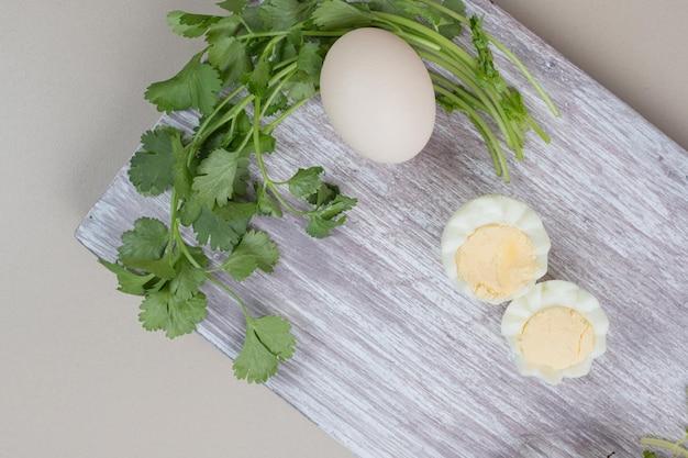 Gekookt ei met ongekookt ei op houten snijplank.